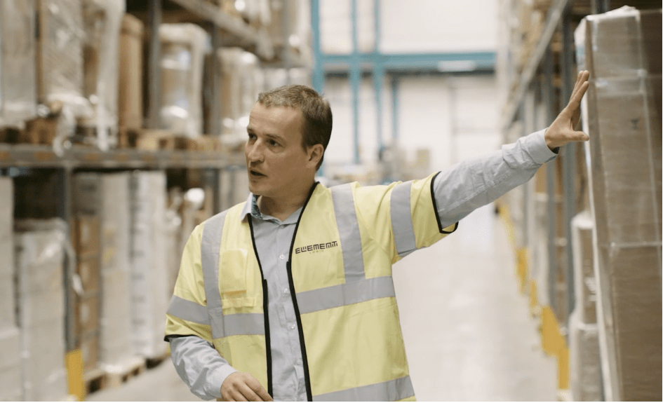 A man in a yellow west in a warehouse is pointing and looking at something outside of the camera shot.