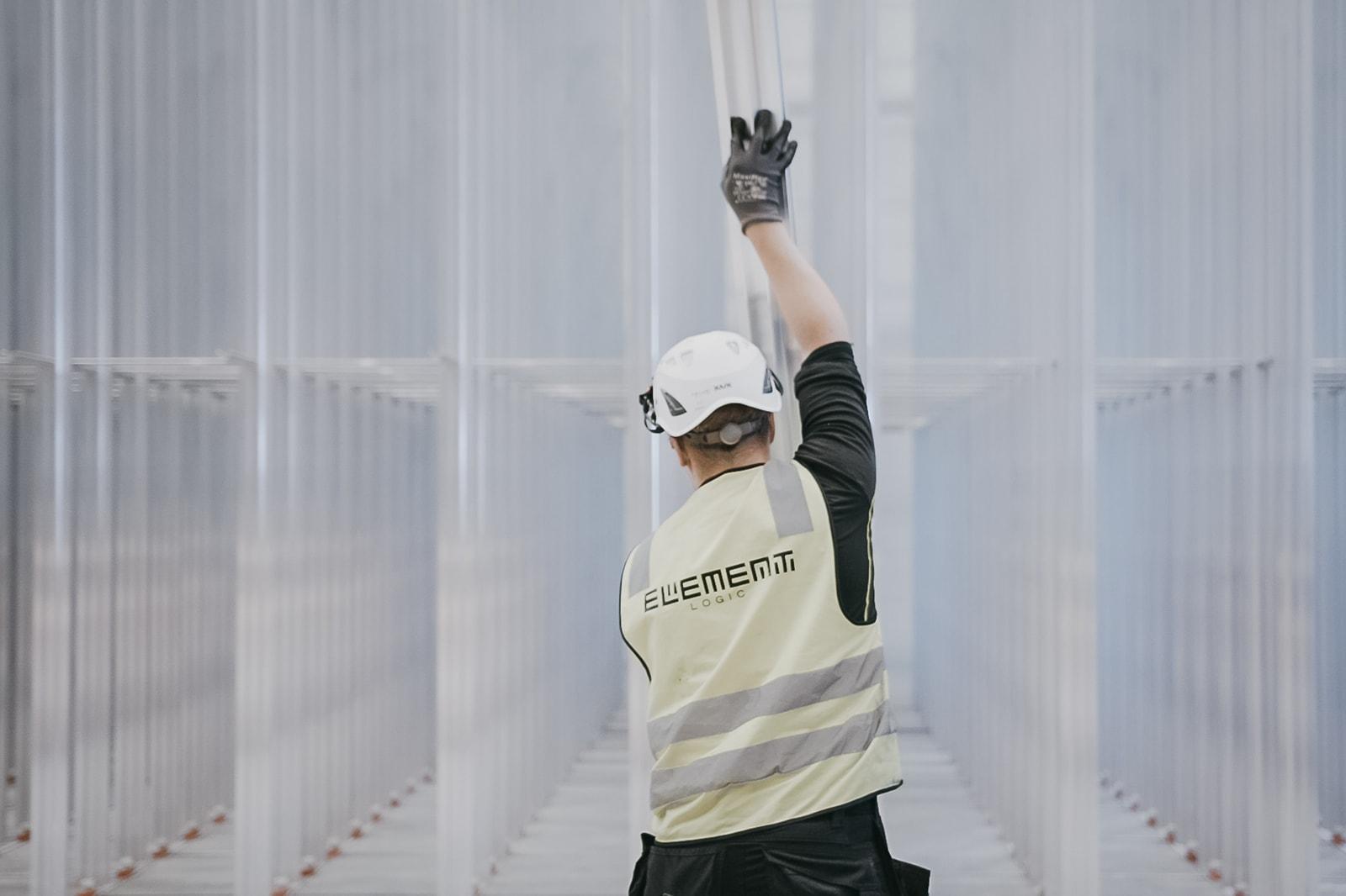 An Element Logic employee assembles the aluminum columns in an AutoStore grid.